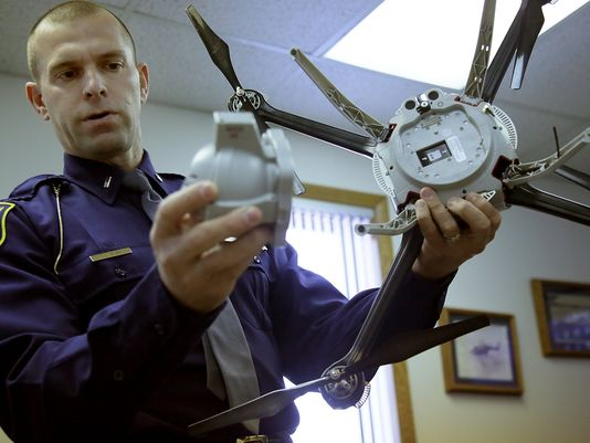 First Lt. Chris Bush, Michigan State Police Commander  of Field Support and Aviation Section, holds an unmanned aerial vehicle that the police force has been training with since 2013 regulated by the Federal Aviation Administration at the Michigan State Police headquarters in Lansing, Mich. on Friday, Nov. 21, 2014. The UAV has a infared camera attached for viewing. (Photo: Kimberly P. Mitchell)